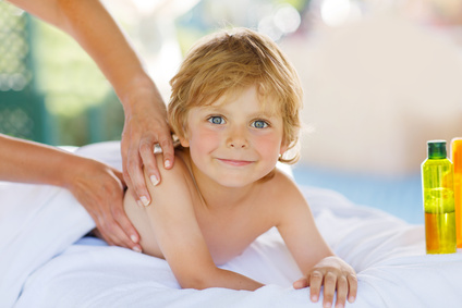 Adorable little blond kid relaxing in spa with having thai massage.