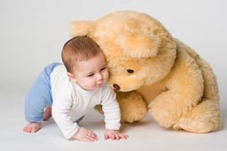 Little boy and yellow bear on white